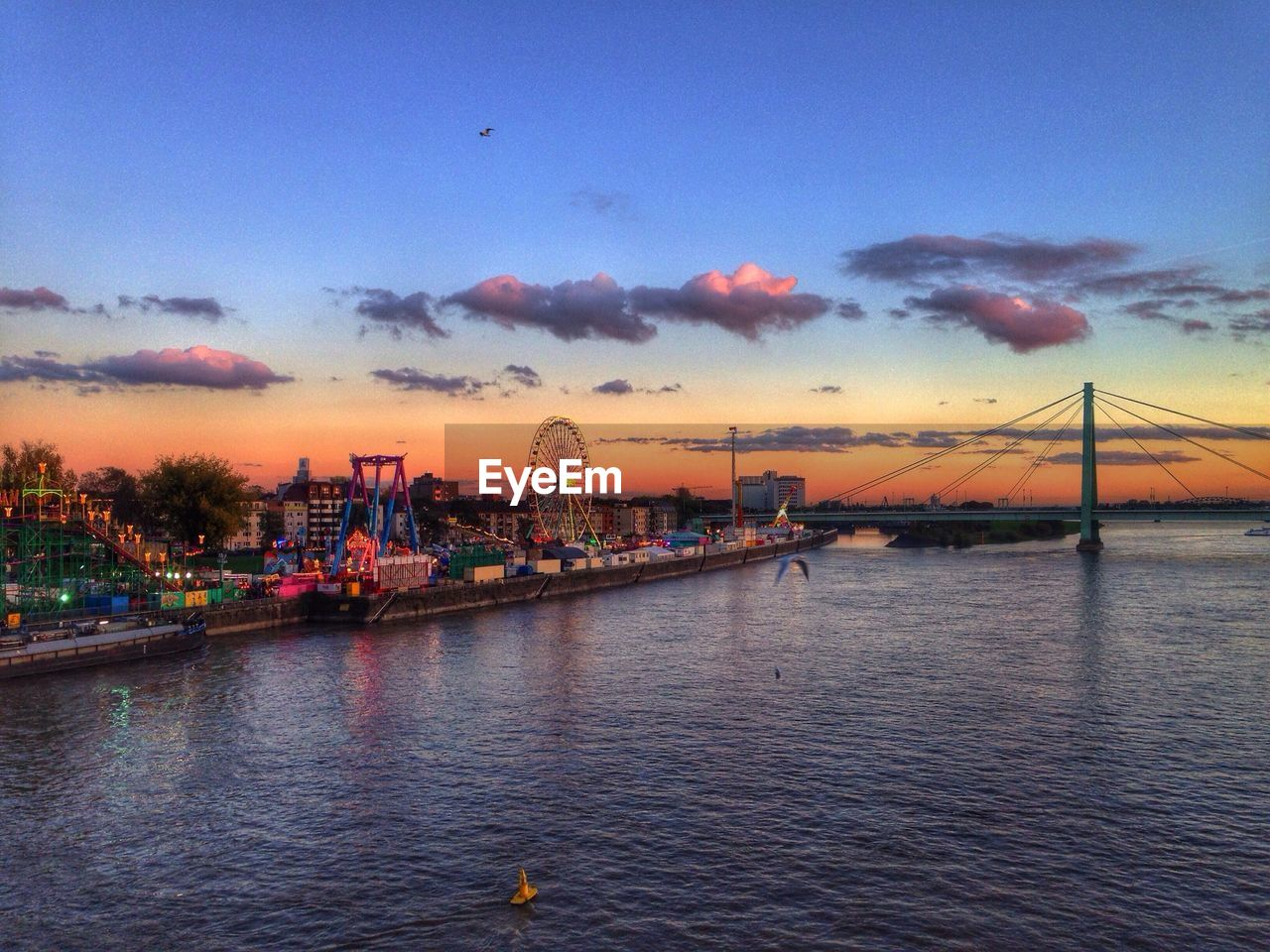 Cityscape with river and amusement park at sunset