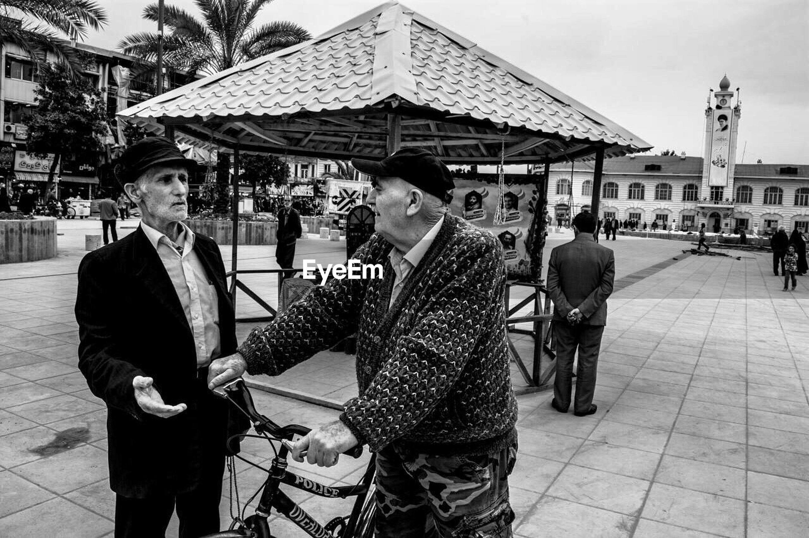 lifestyles, building exterior, casual clothing, leisure activity, built structure, architecture, togetherness, men, city, person, bonding, full length, love, street, standing, city life, young men