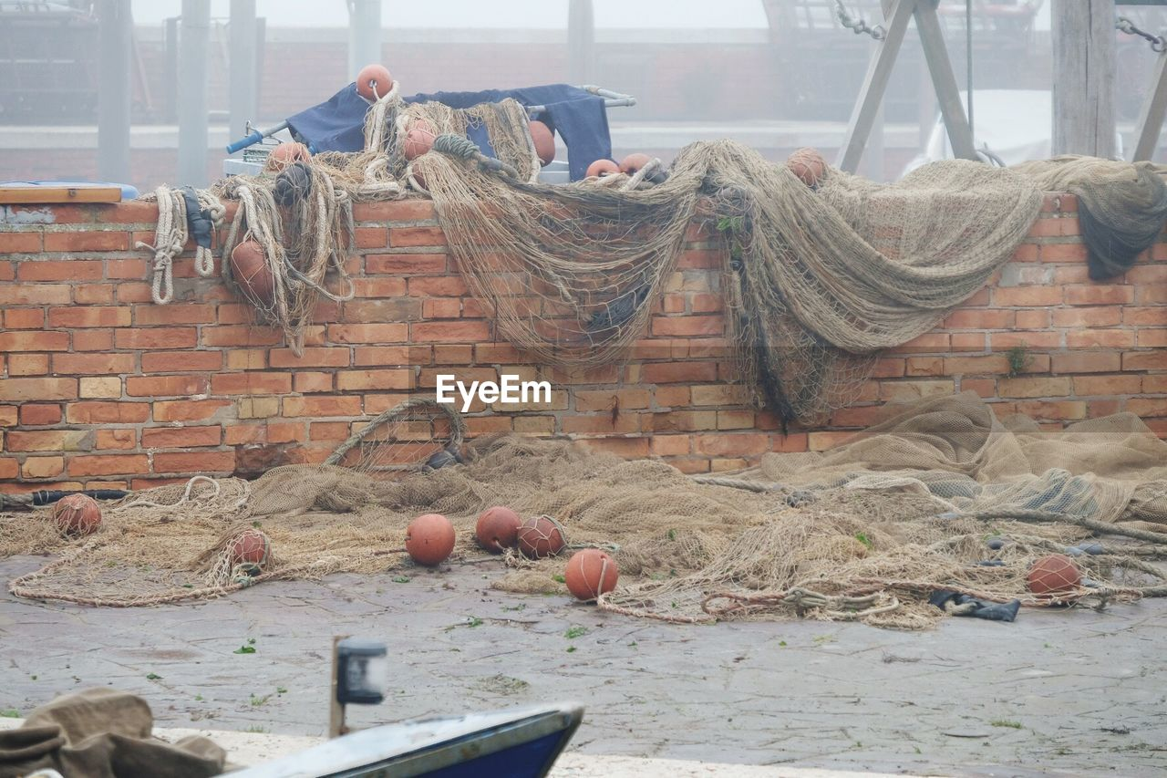 day, no people, architecture, nature, built structure, textile, building exterior, outdoors, water, window, wall, drying, fishing net, hanging, brick, blanket, relaxation, clothing, fishing industry