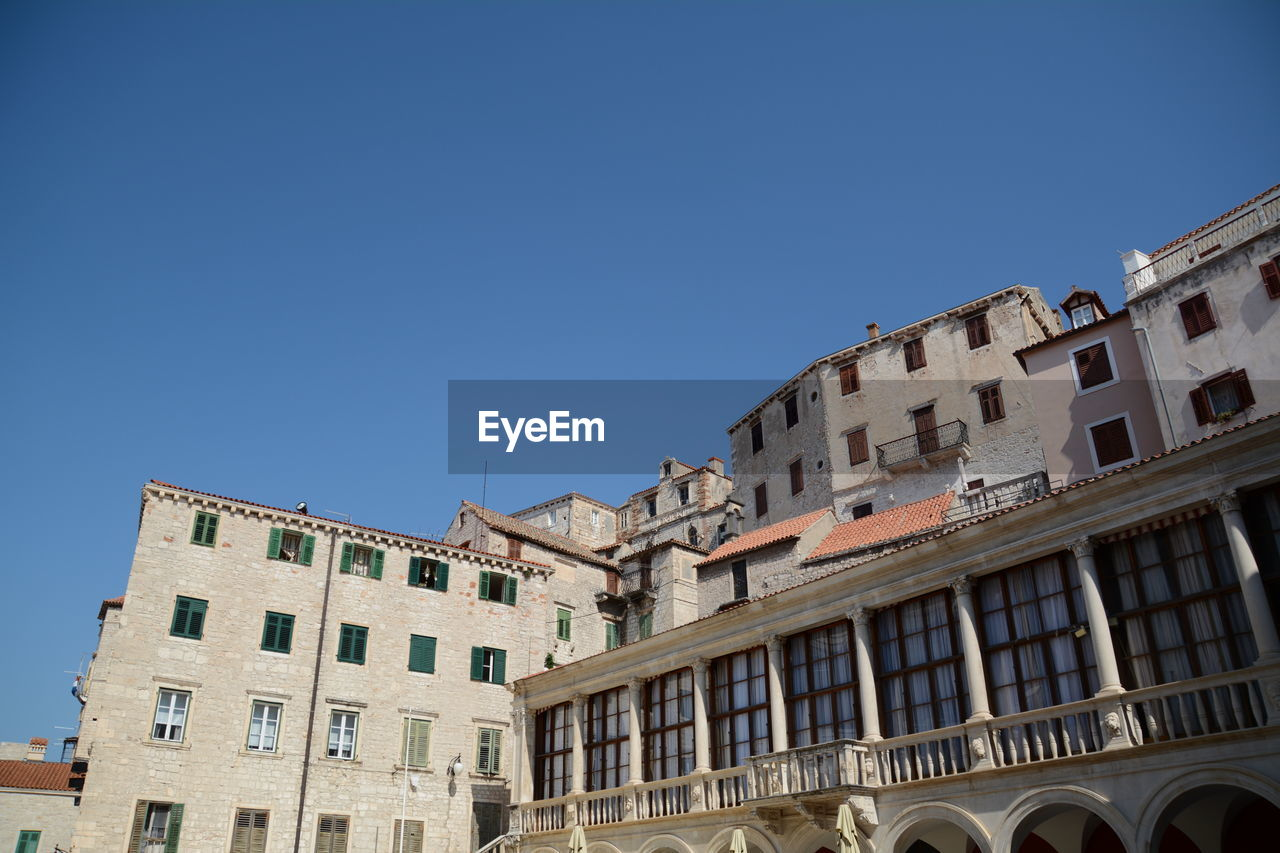 architecture, building exterior, built structure, sky, blue, low angle view, copy space, clear sky, building, window, day, nature, no people, city, sunlight, outdoors, history, the past, arch, residential district, apartment