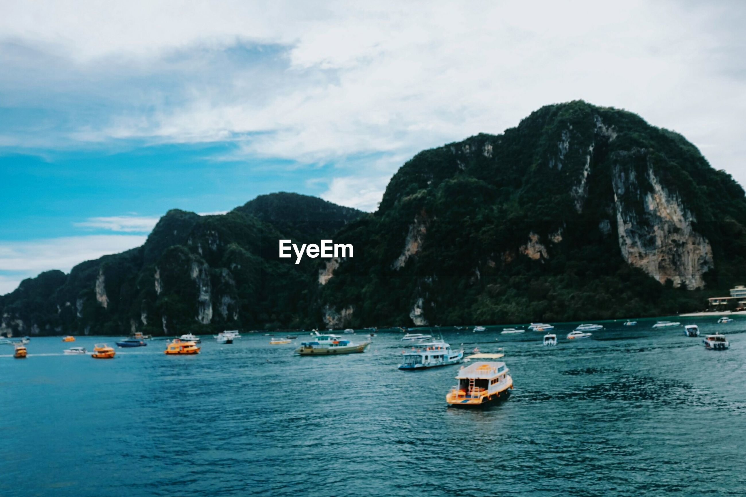 BOATS IN SEA AGAINST MOUNTAINS