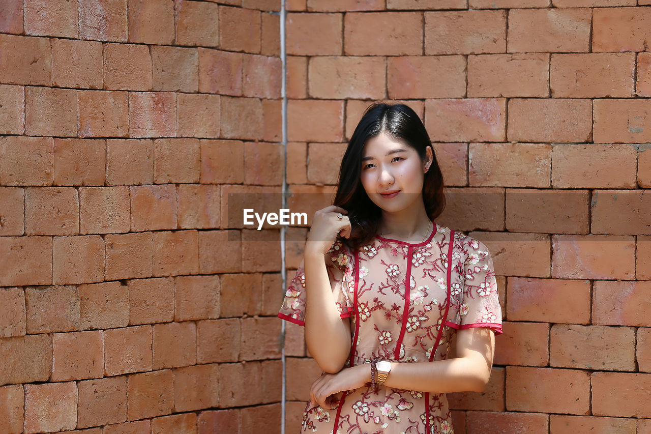 young adult, brick, one person, wall, brick wall, wall - building feature, young women, front view, casual clothing, standing, lifestyles, real people, beautiful woman, women, leisure activity, looking at camera, beauty, portrait, hair, hairstyle, teenager, floral pattern