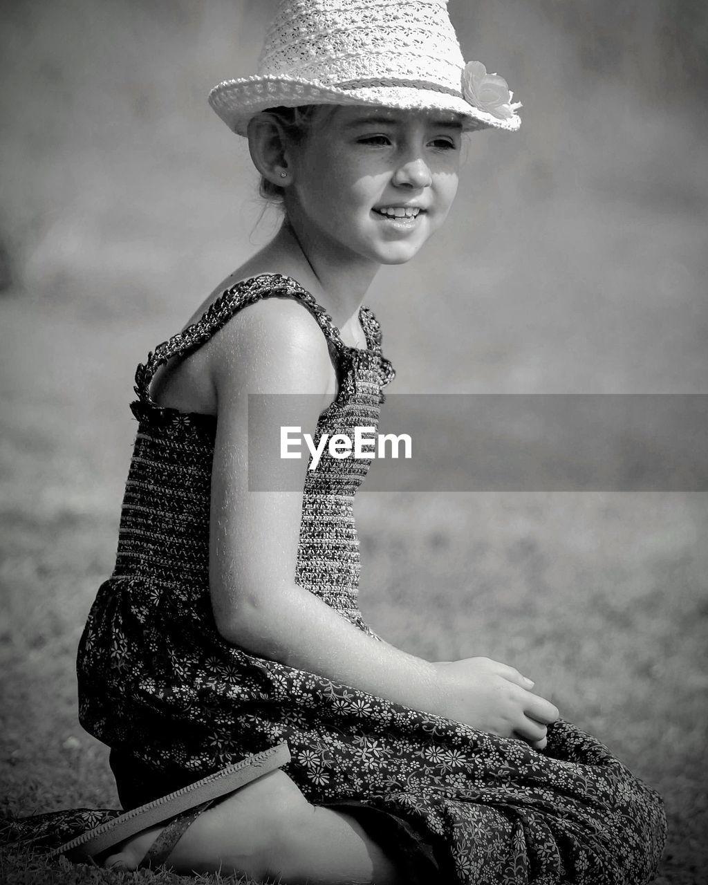 Smiling girl wearing hat kneeling on land