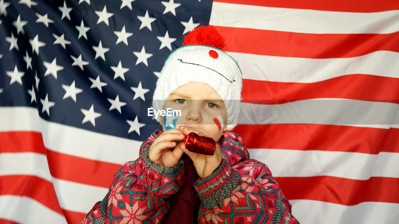 Close-Up Portrait Of Girl With Party Horn Blower Against American Flag