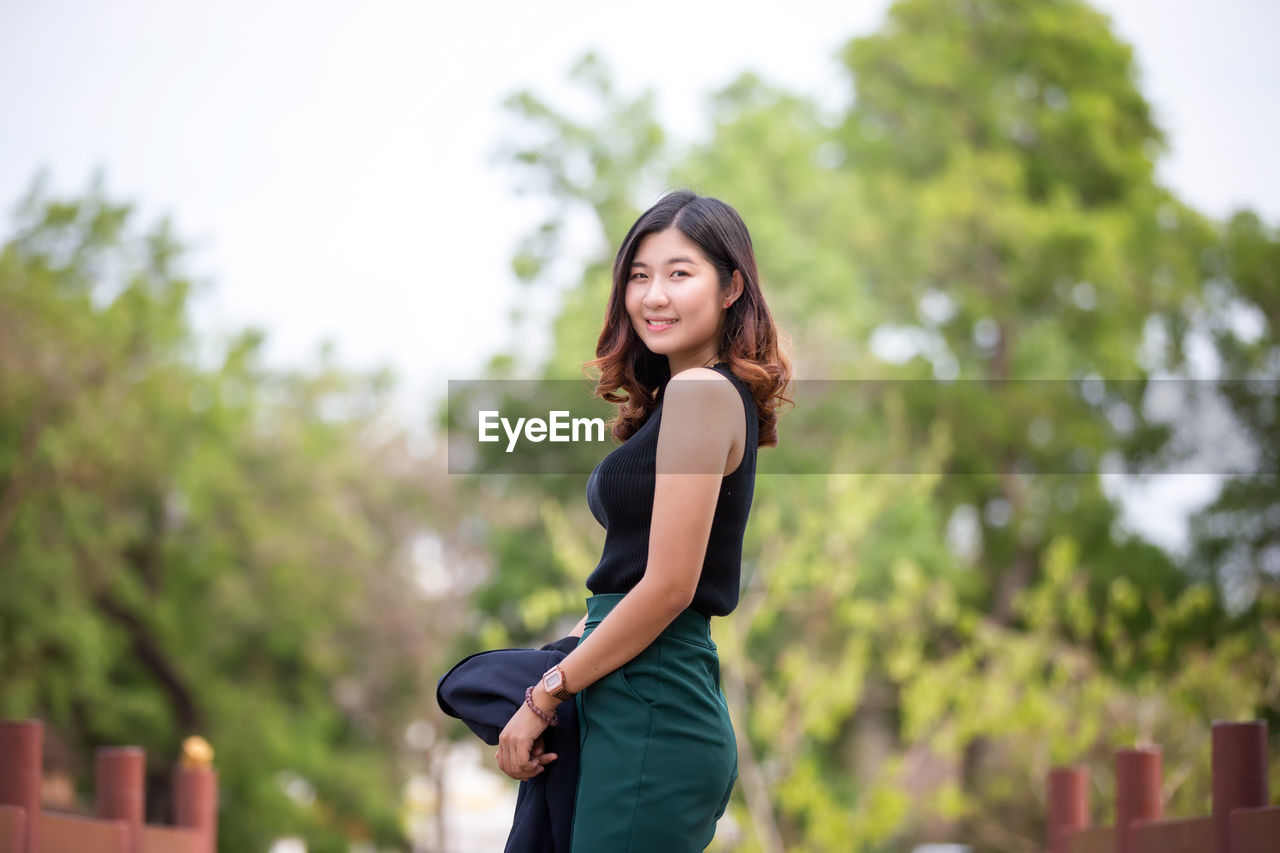 young adult, focus on foreground, one person, young women, three quarter length, women, lifestyles, real people, standing, side view, looking at camera, adult, day, leisure activity, casual clothing, plant, portrait, smiling, hair, beautiful woman, hairstyle, outdoors