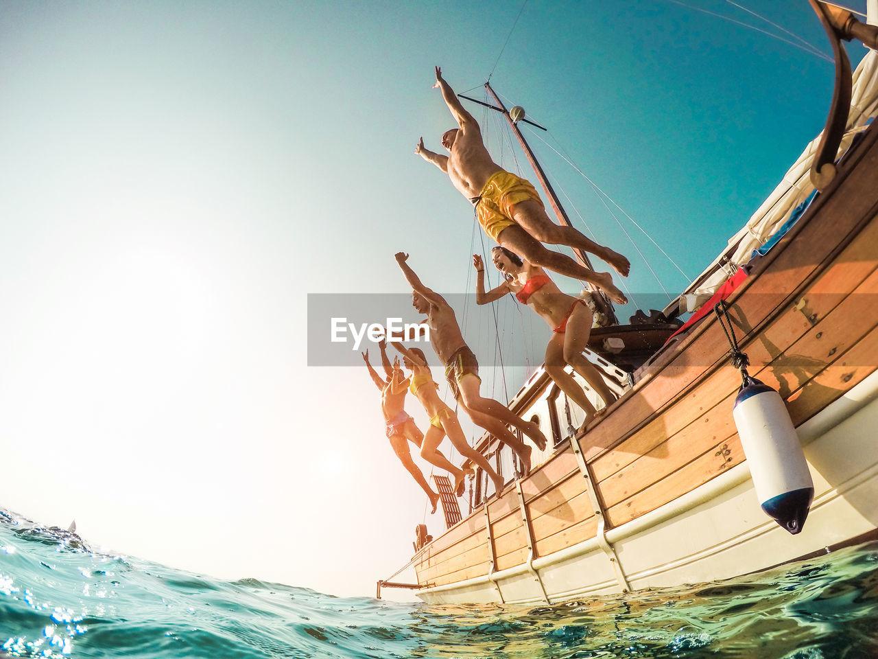 People Jumping In Sea Against Sky
