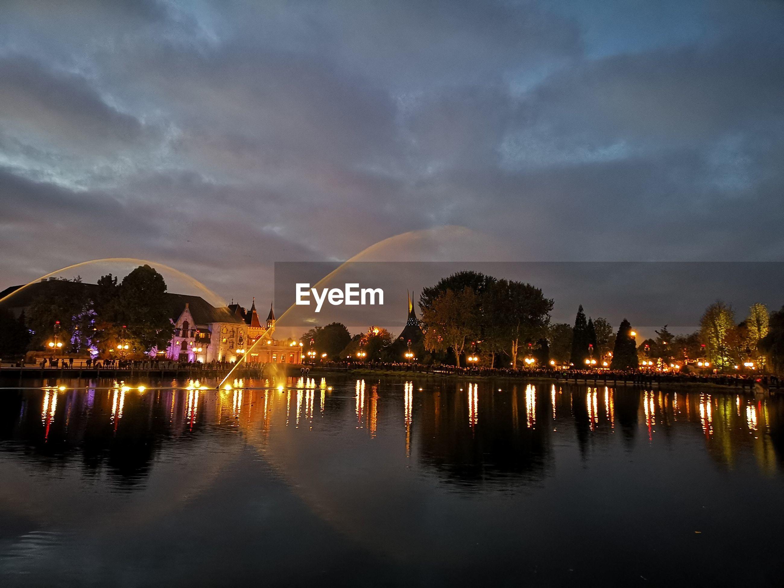 Lake in illuminated city at night