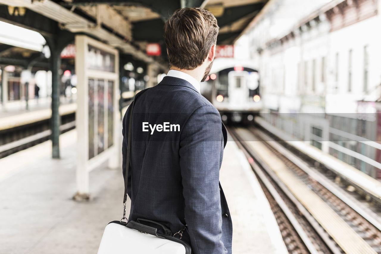 REAR VIEW OF MAN AT RAILROAD STATION