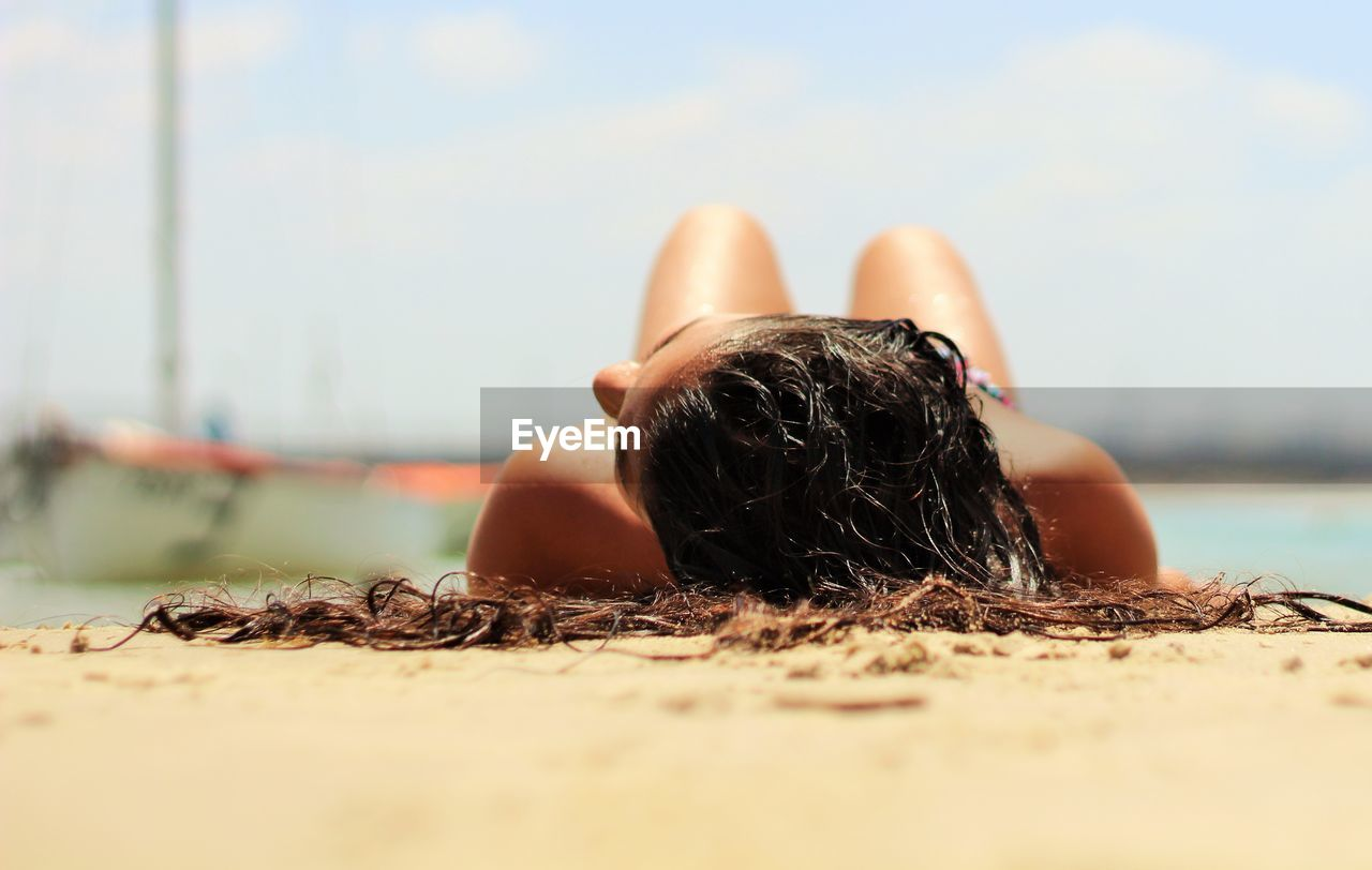 Woman resting on beach during sunny day
