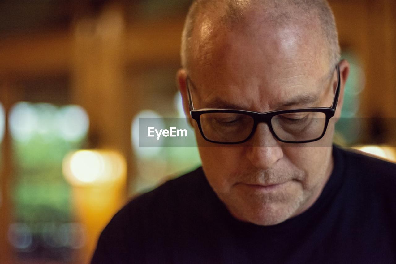 Close-up of mature man wearing eyeglasses at home