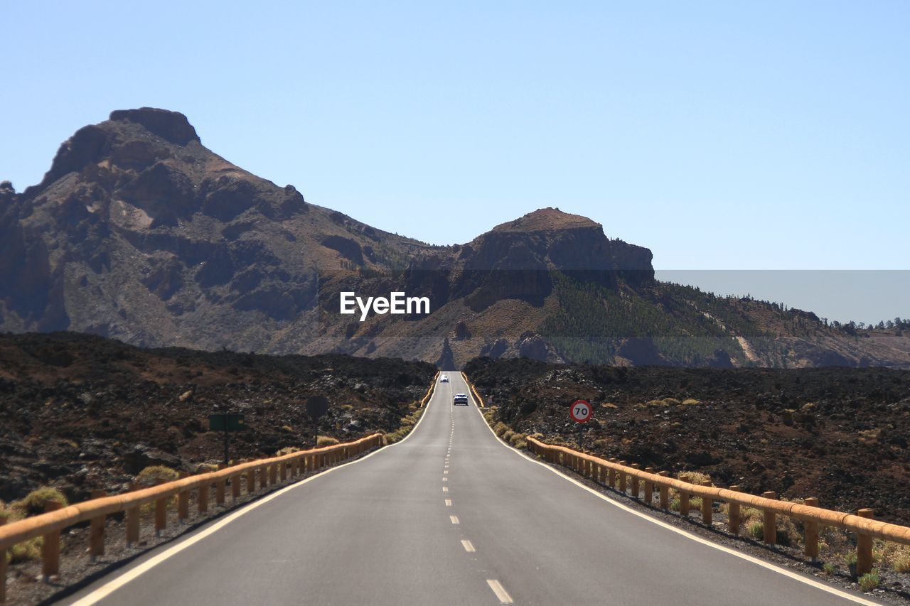 Empty road leading towards mountains against clear sky