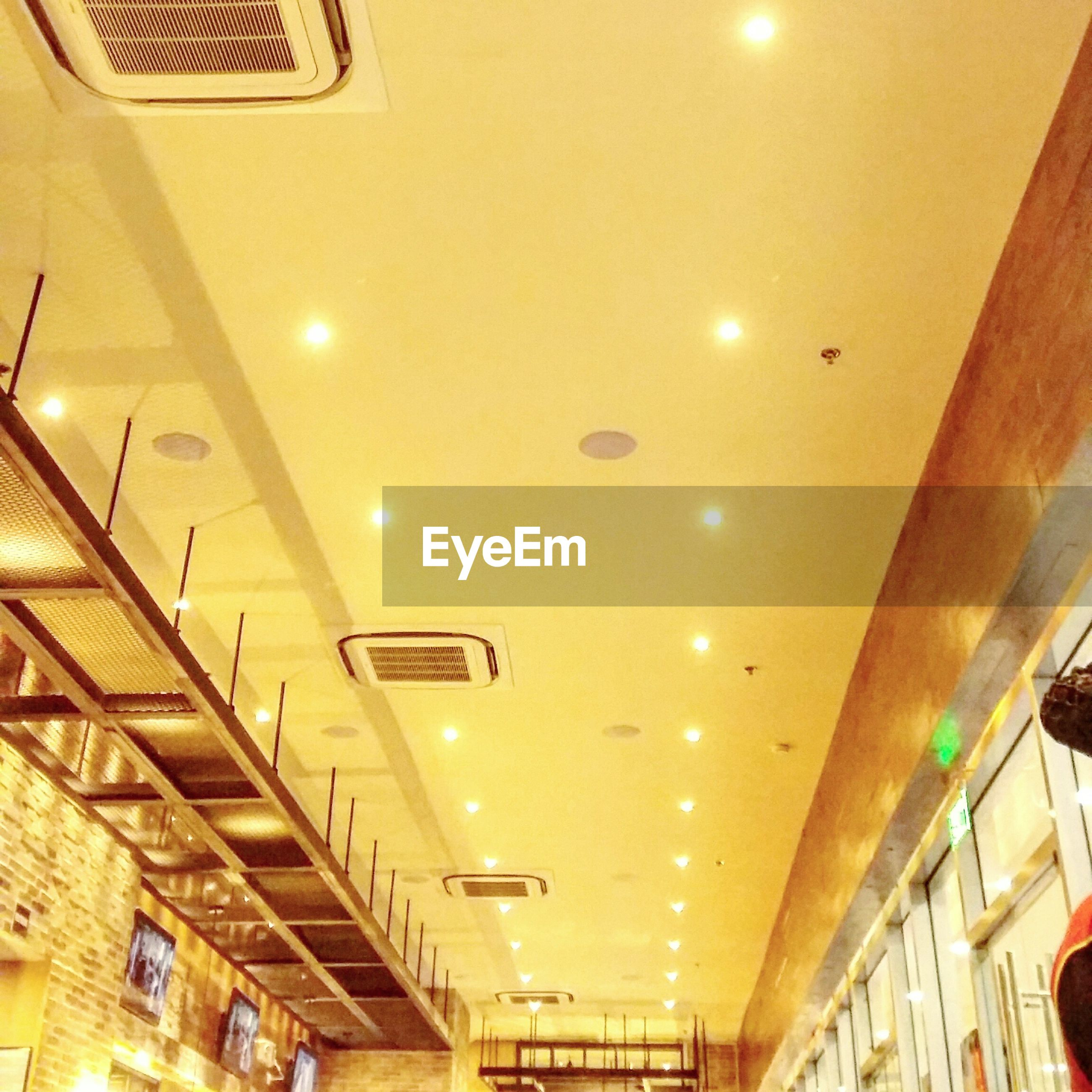 indoors, ceiling, illuminated, lighting equipment, low angle view, modern, hanging, diminishing perspective, architecture, architectural feature, convenience, corridor, lobby, airport, theater, light fixture, hanging light, museum, electric light, fairy lights, famous place, recessed light