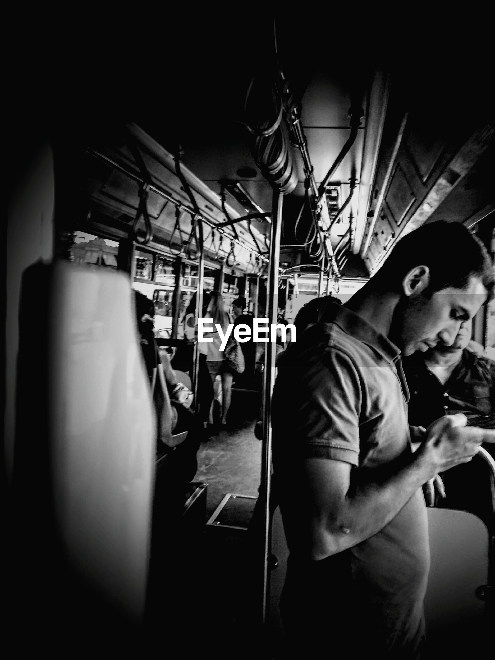 Side view of man using mobile phone while standing in bus