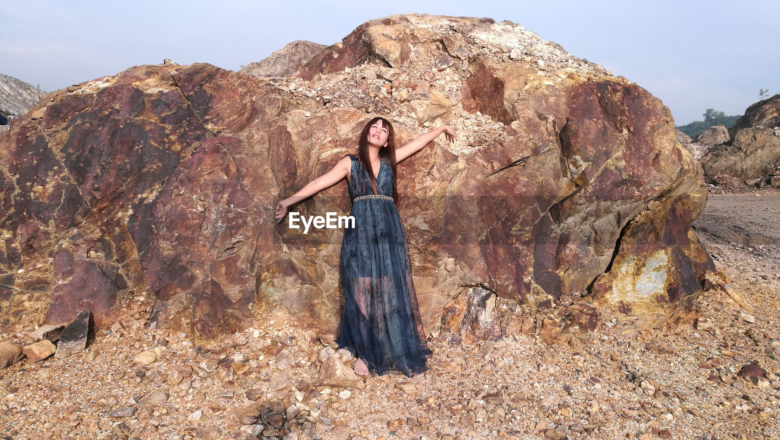 Full length of woman standing against rock