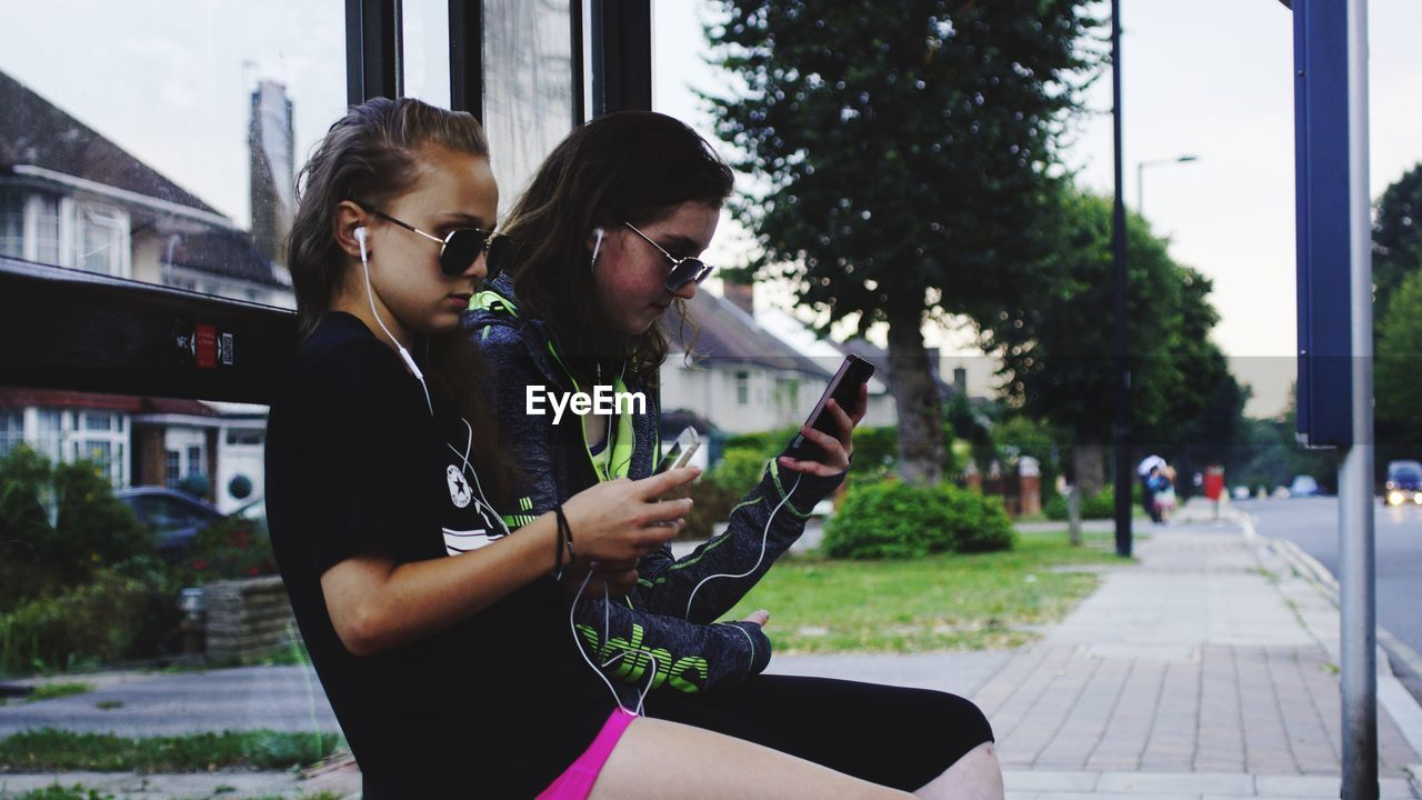 Teenagers Sitting At Bus Stop While Listening At Music From Mobile Phone