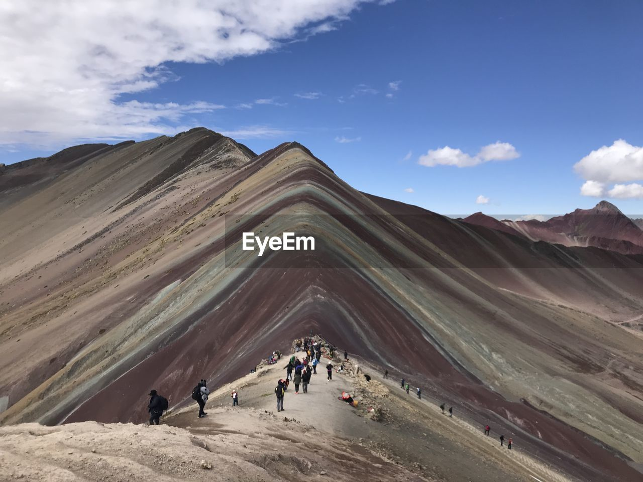 Group of people on mountain against sky