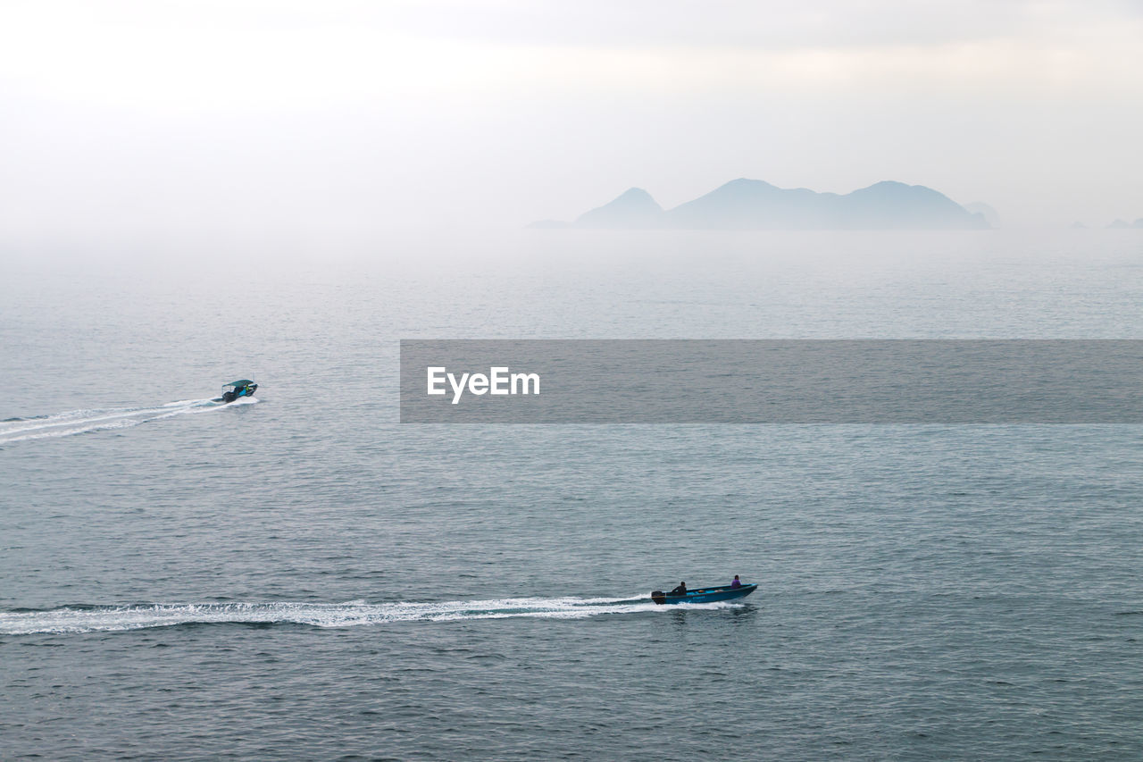 High angle view of boats on sea against sky during foggy weather