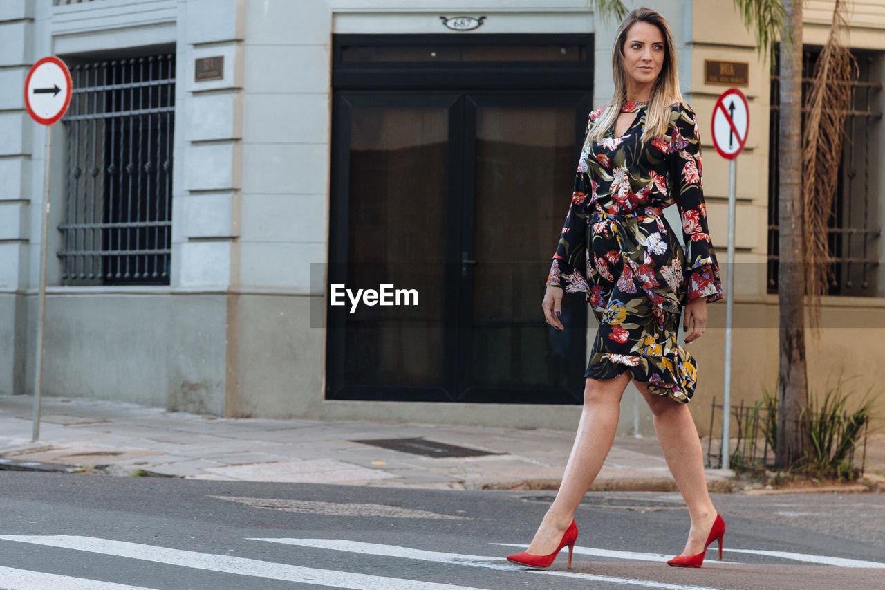 Woman crossing on street in city