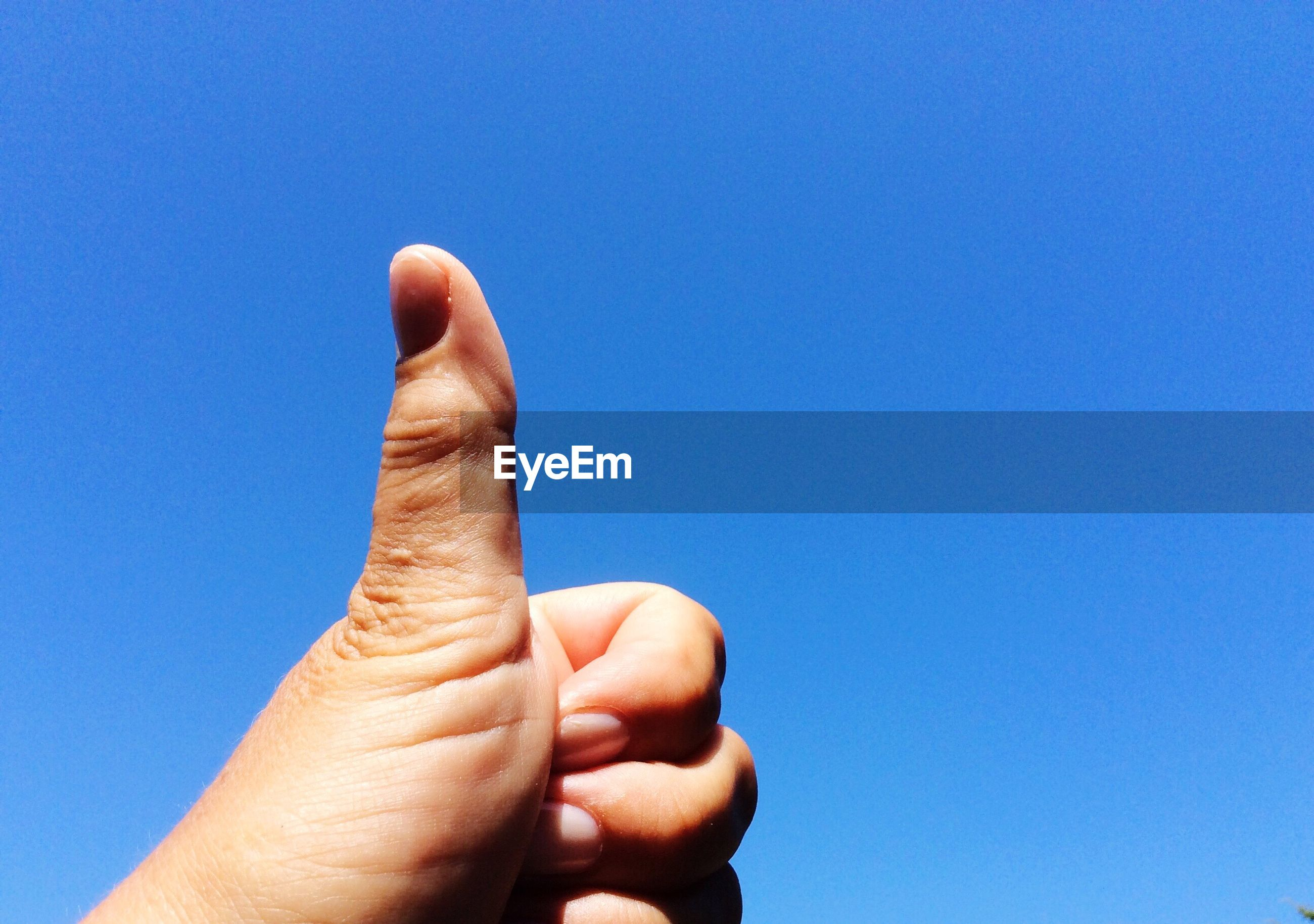 Cropped image of hand showing thumbs up against clear blue sky
