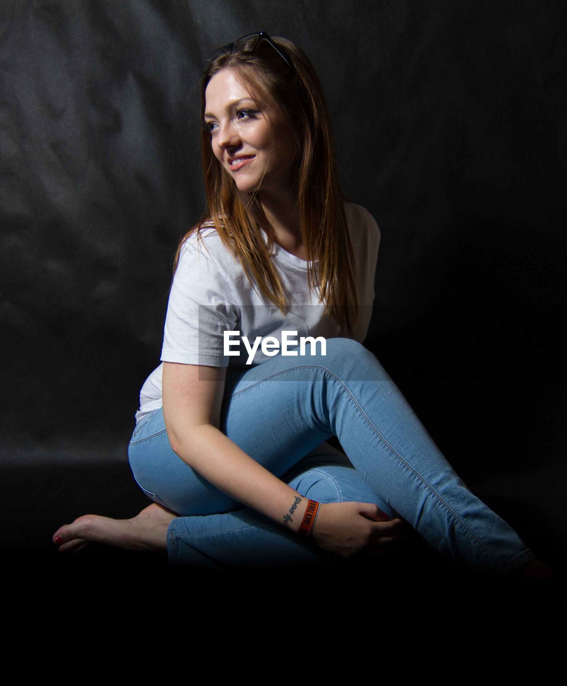 Smiling young woman sitting against black background