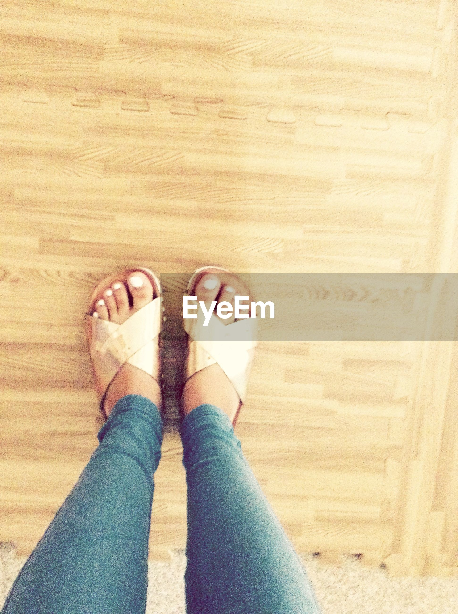 person, low section, personal perspective, human foot, lifestyles, shoe, high angle view, leisure activity, standing, barefoot, part of, jeans, indoors, footwear, fashion, directly above