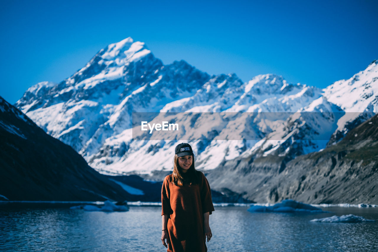 Young girl standing next lake shore with snowcapped mountain at the back.