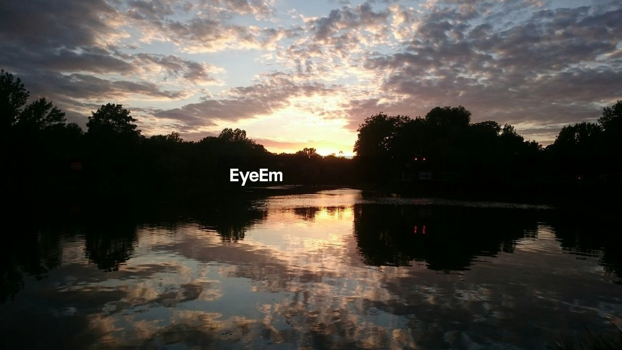 Scenic view of lake with clouds reflection at sunset