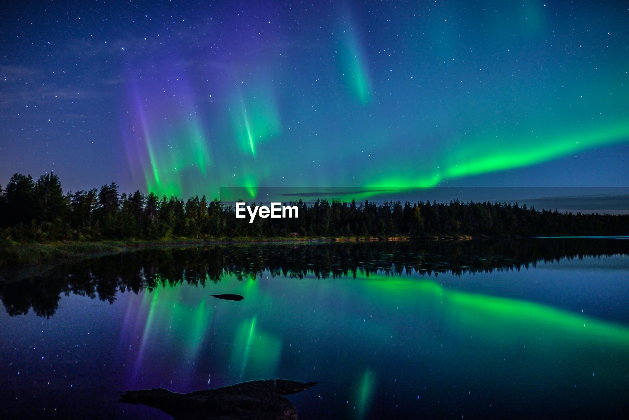 Scenic view of lake against aurora borealis at night