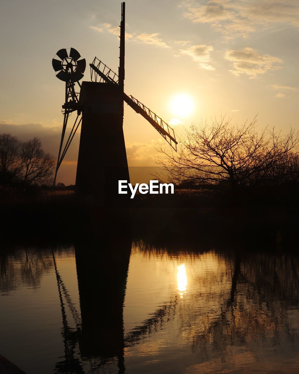 sunset, environmental conservation, alternative energy, reflection, wind power, wind turbine, windmill, renewable energy, fuel and power generation, silhouette, traditional windmill, sky, orange color, water, no people, tranquility, tranquil scene, beauty in nature, scenics, nature, lake, outdoors, waterfront, cloud - sky, rural scene, industrial windmill, tree, technology, day