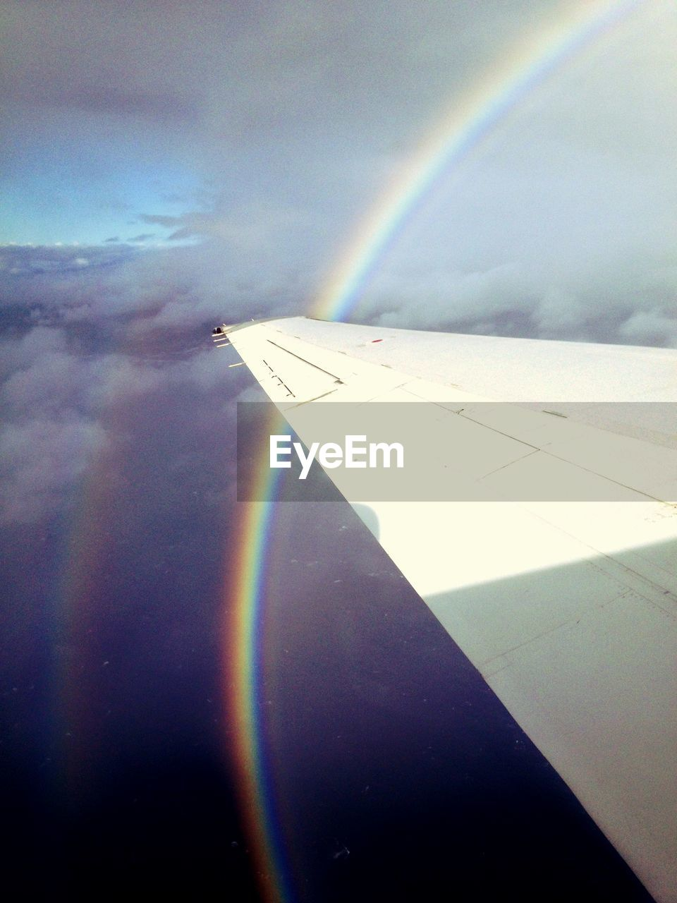 Cropped image of airplane against rainbow in cloudy sky