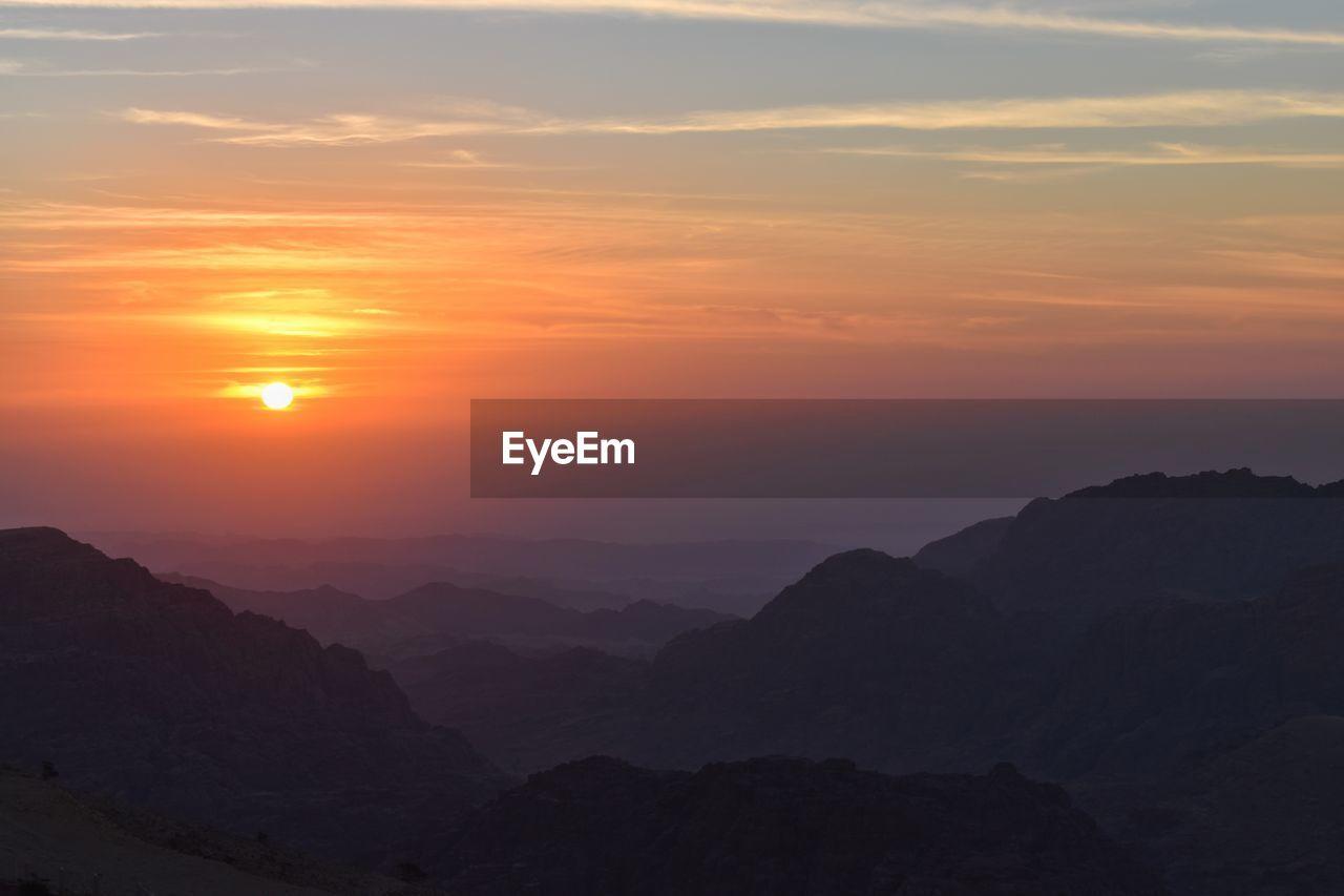 sunset, beauty in nature, scenics - nature, sky, tranquil scene, mountain, tranquility, idyllic, orange color, mountain range, cloud - sky, non-urban scene, nature, sun, no people, silhouette, environment, majestic, outdoors, landscape, mountain peak, romantic sky