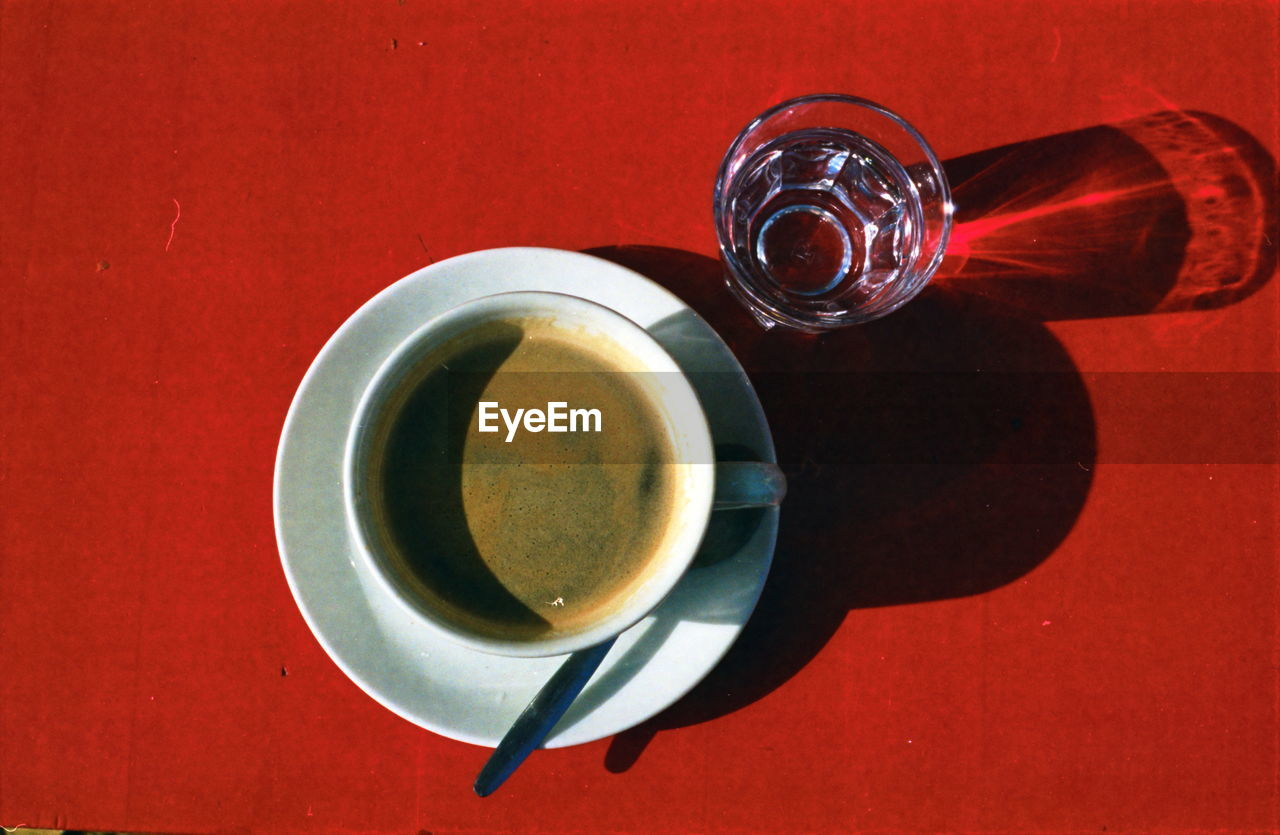 Coffee and glass of water on red table