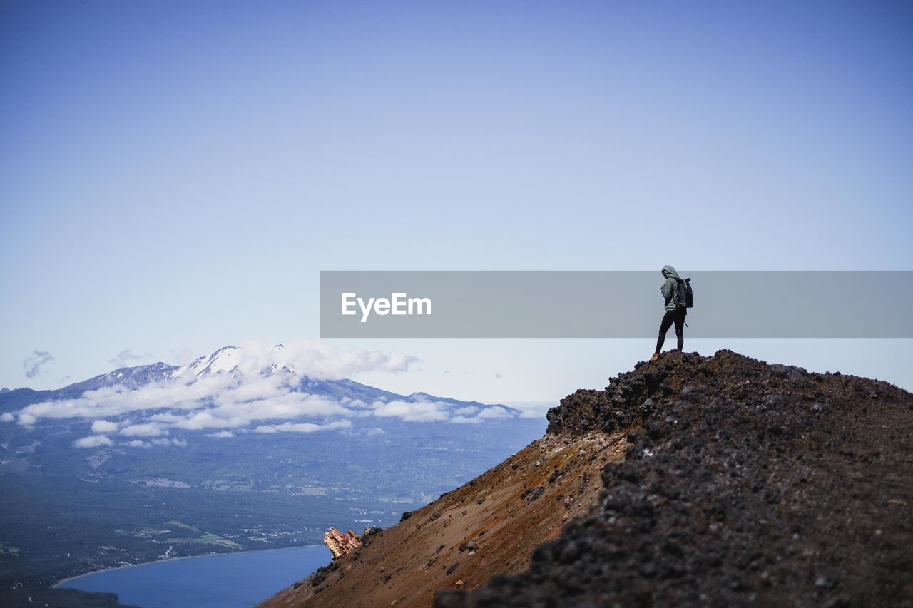 MAN STANDING ON ROCKS AGAINST MOUNTAIN