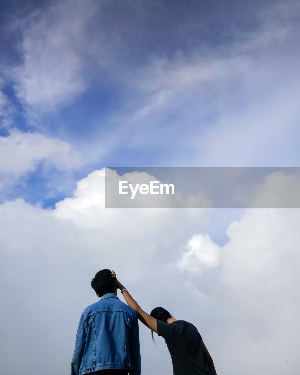 Low angle view of friends standing against cloudy sky
