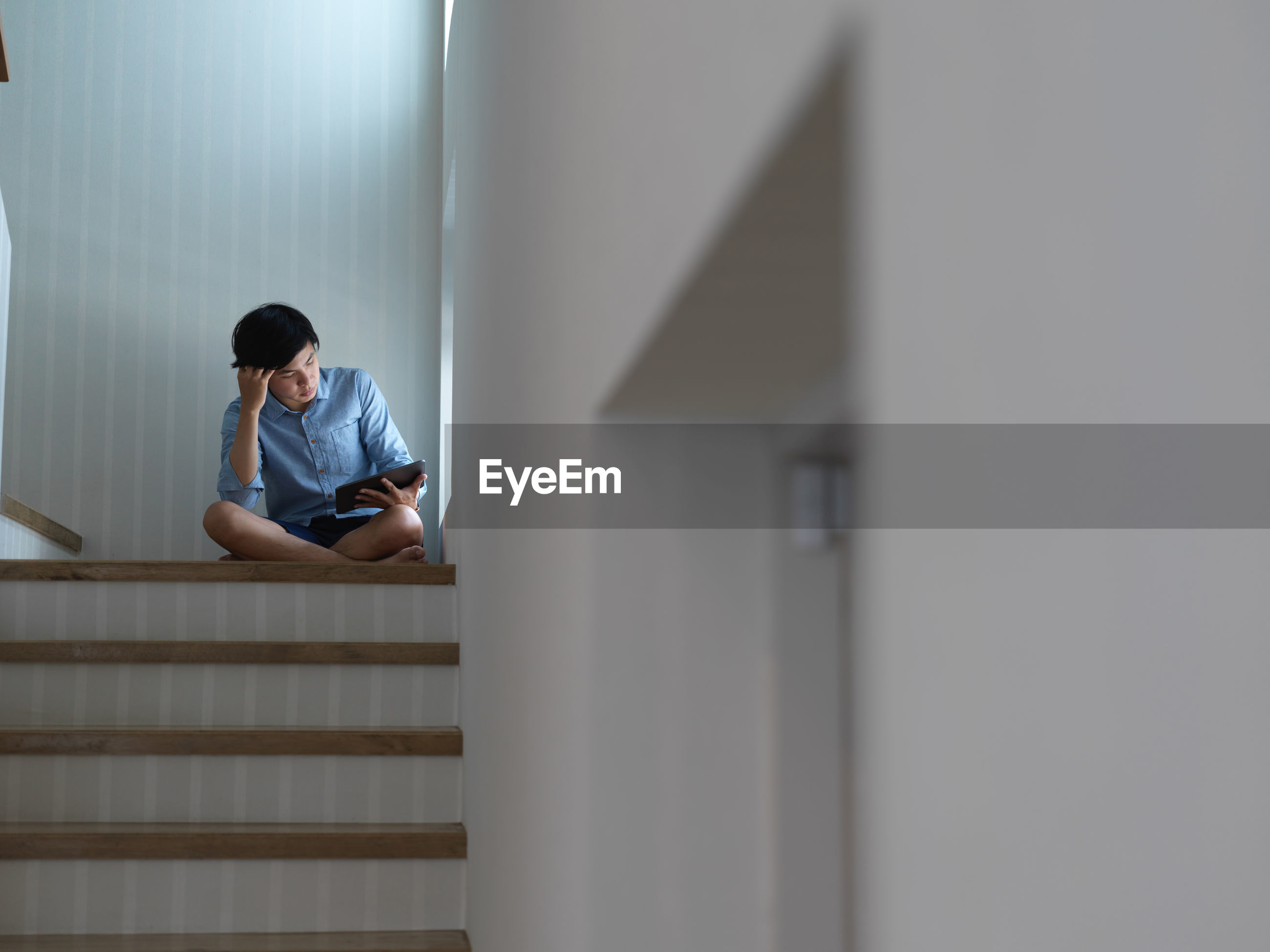 Low angel view of young man holding digital tablet sitting on staircase