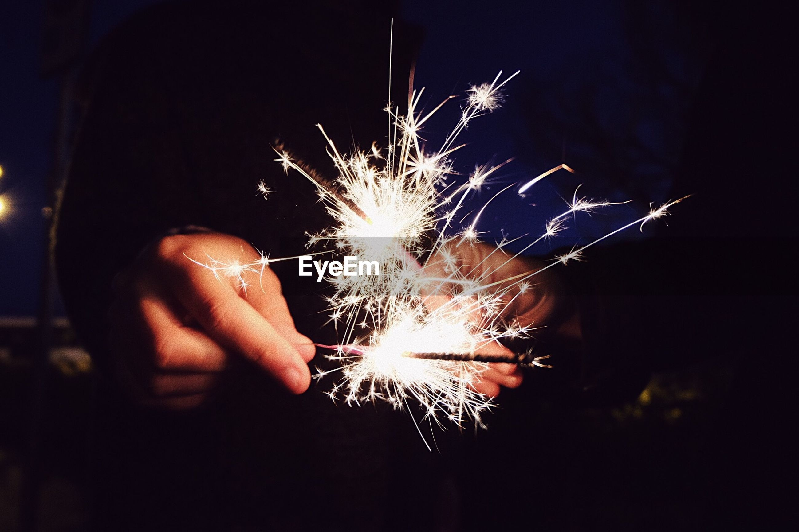Close-up of hands holding sparkler at night