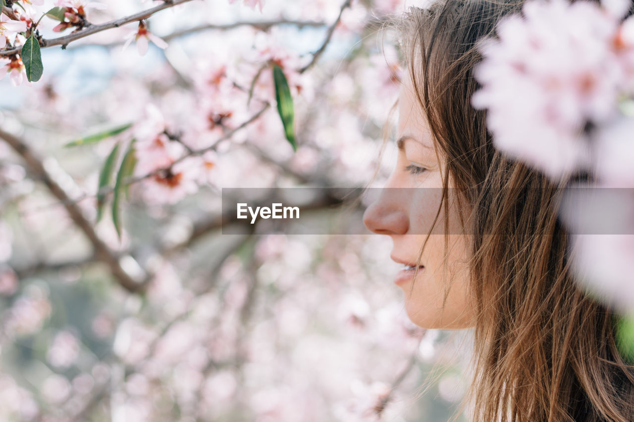 Close-up of young woman with flowers on tree