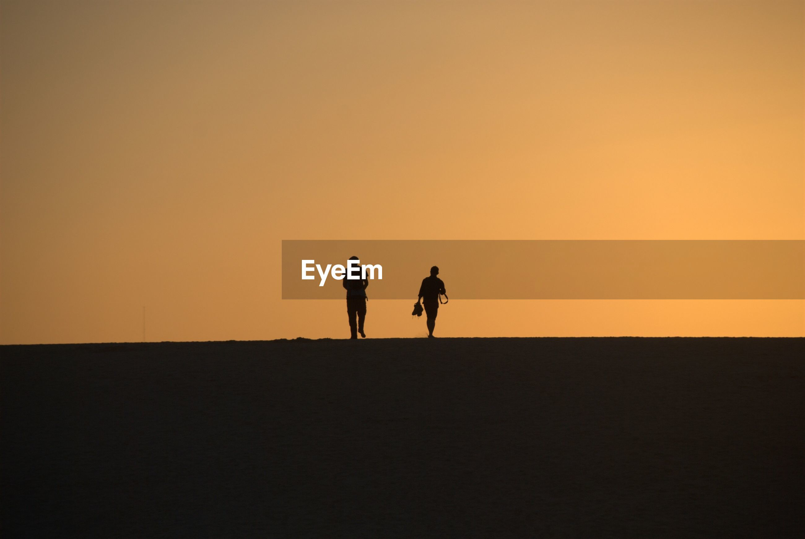 Silhouette of people walking against sky during sunset
