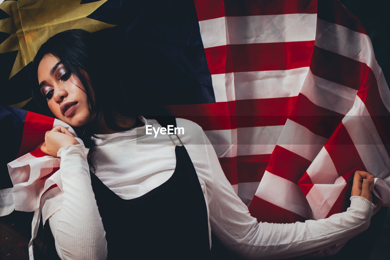 Thoughtful female model posing with malaysian flag on spool