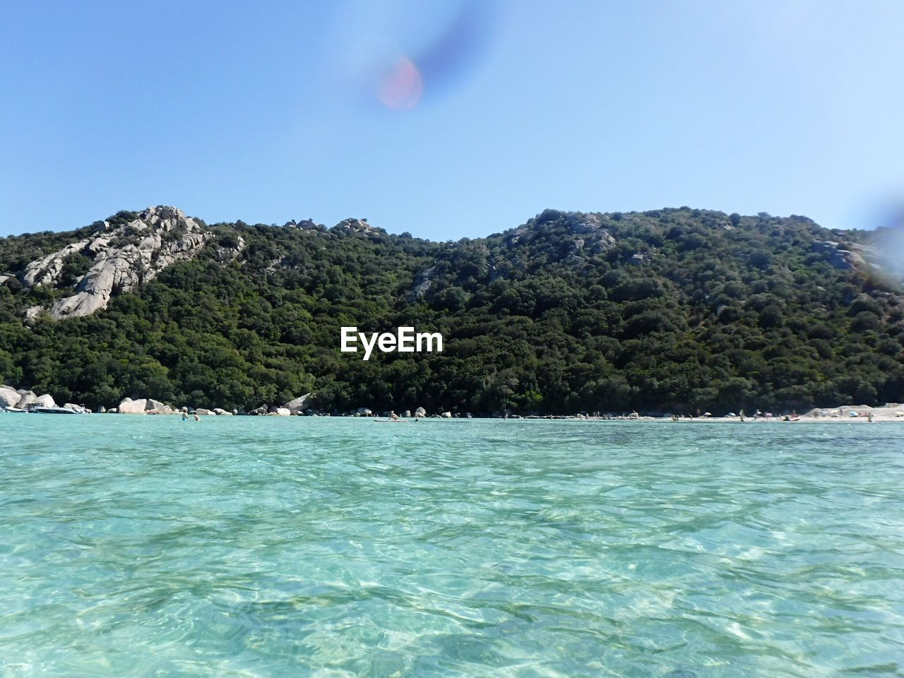 SCENIC VIEW OF SEA BY MOUNTAIN AGAINST CLEAR SKY