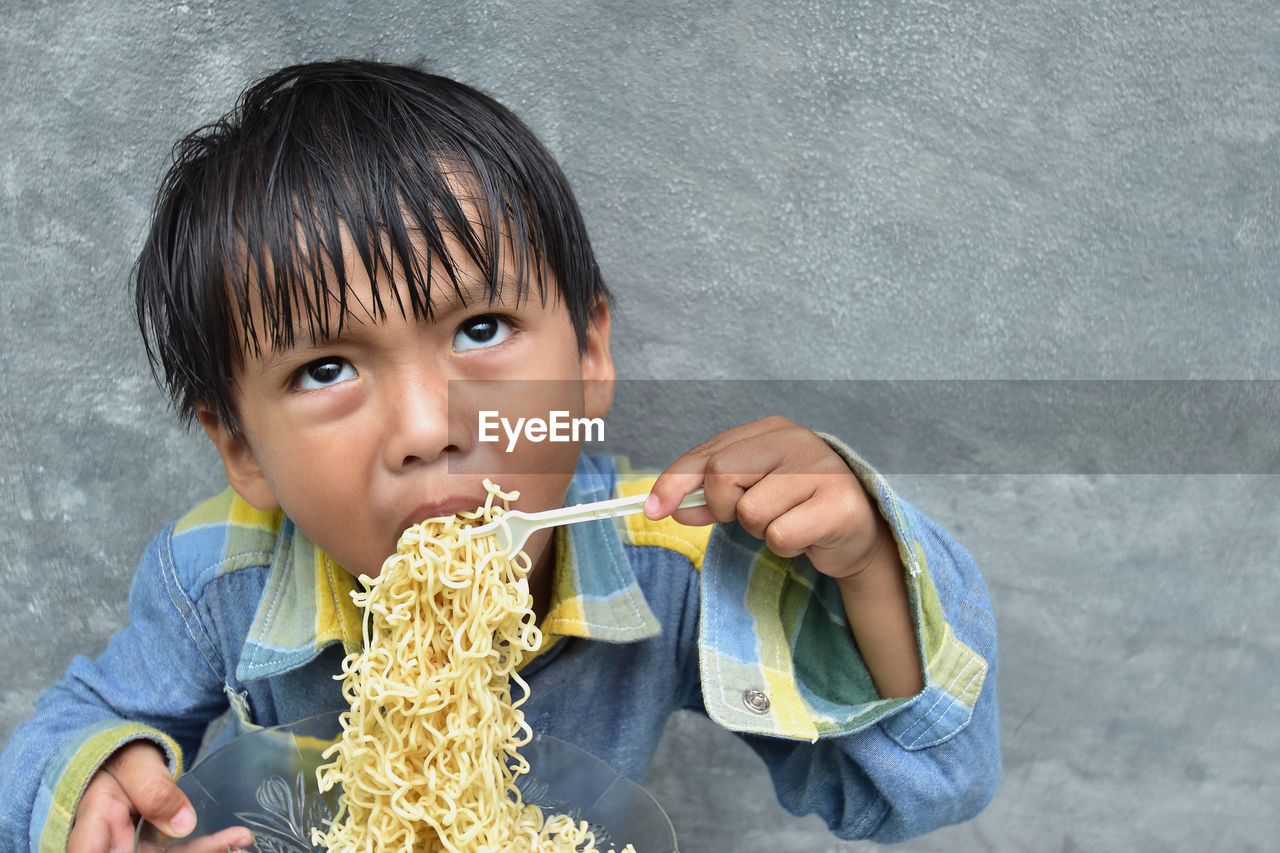 High Angle View Of Boy Eating Noodles Against Wall