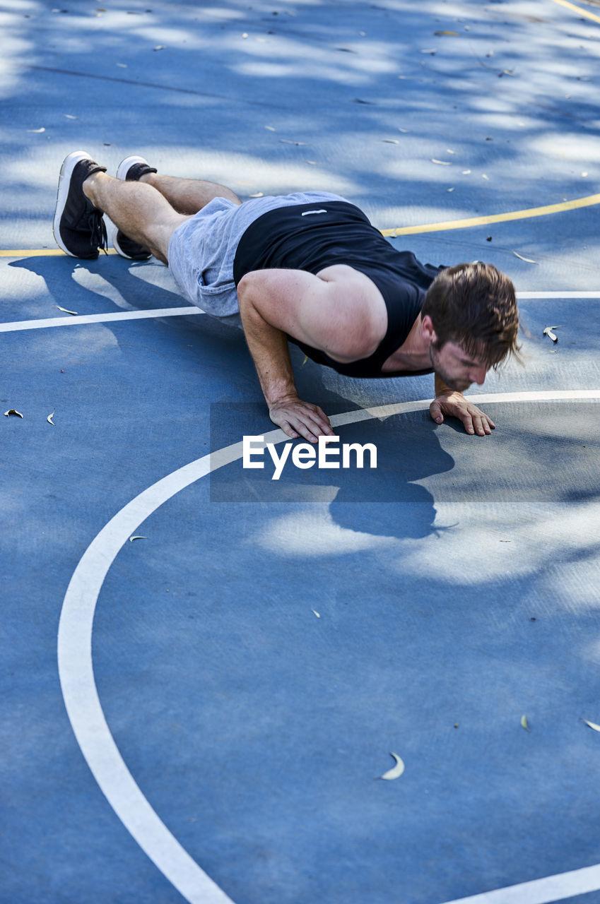 Full Length Of Man Exercising On Court