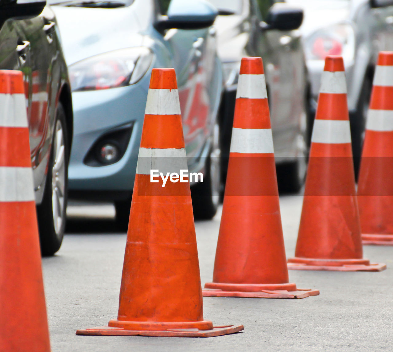 CLOSE-UP OF RED TRAFFIC CONES ON ROAD