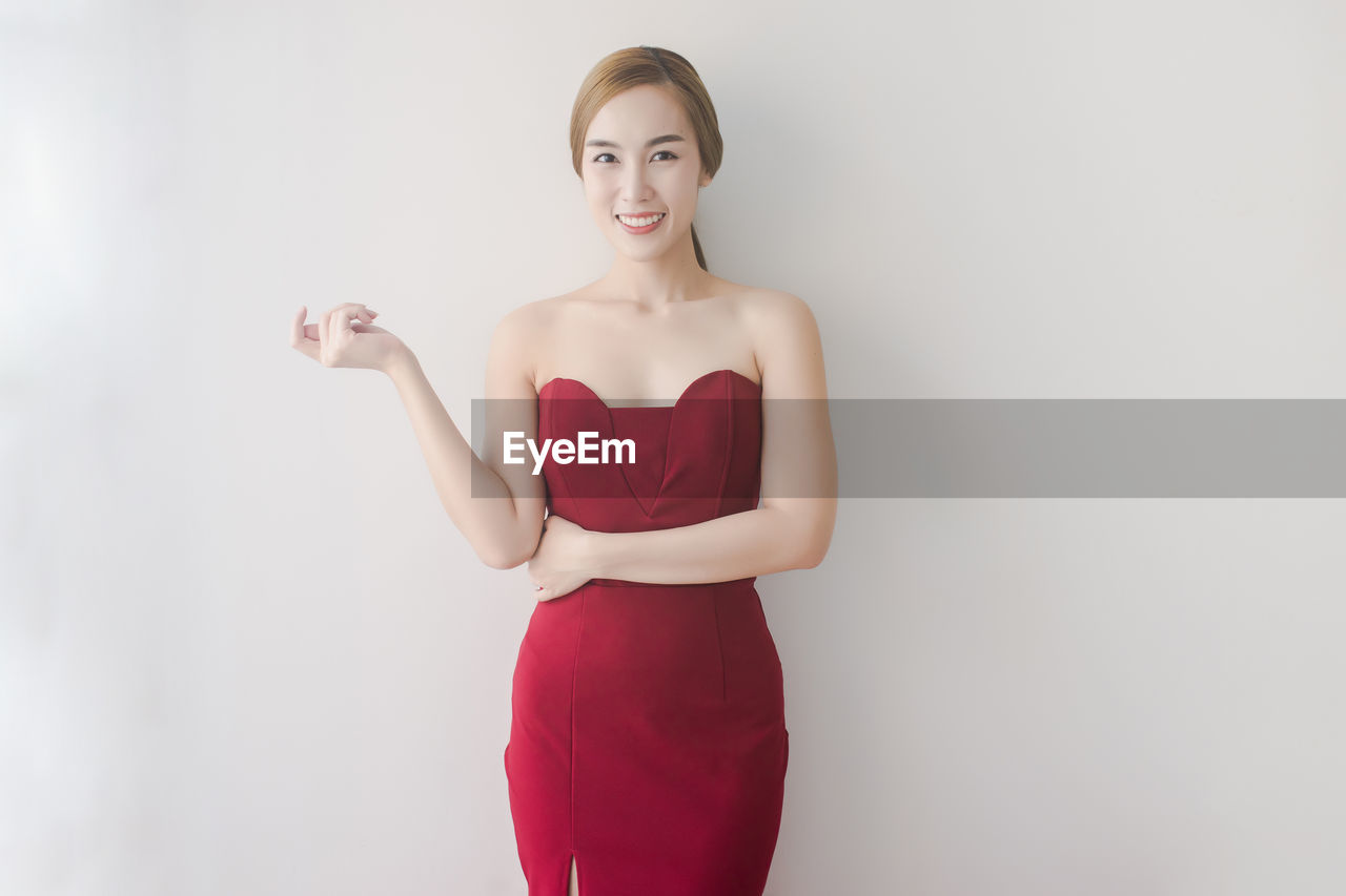 Portrait of young woman wearing red dress while standing against white background