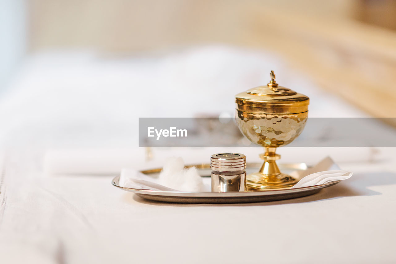 indoors, gold colored, table, no people, still life, focus on foreground, close-up, selective focus, metal, plate, eating utensil, kitchen utensil, antique, household equipment, absence, food and drink, wood - material, high angle view, glass, white color, crockery, setting
