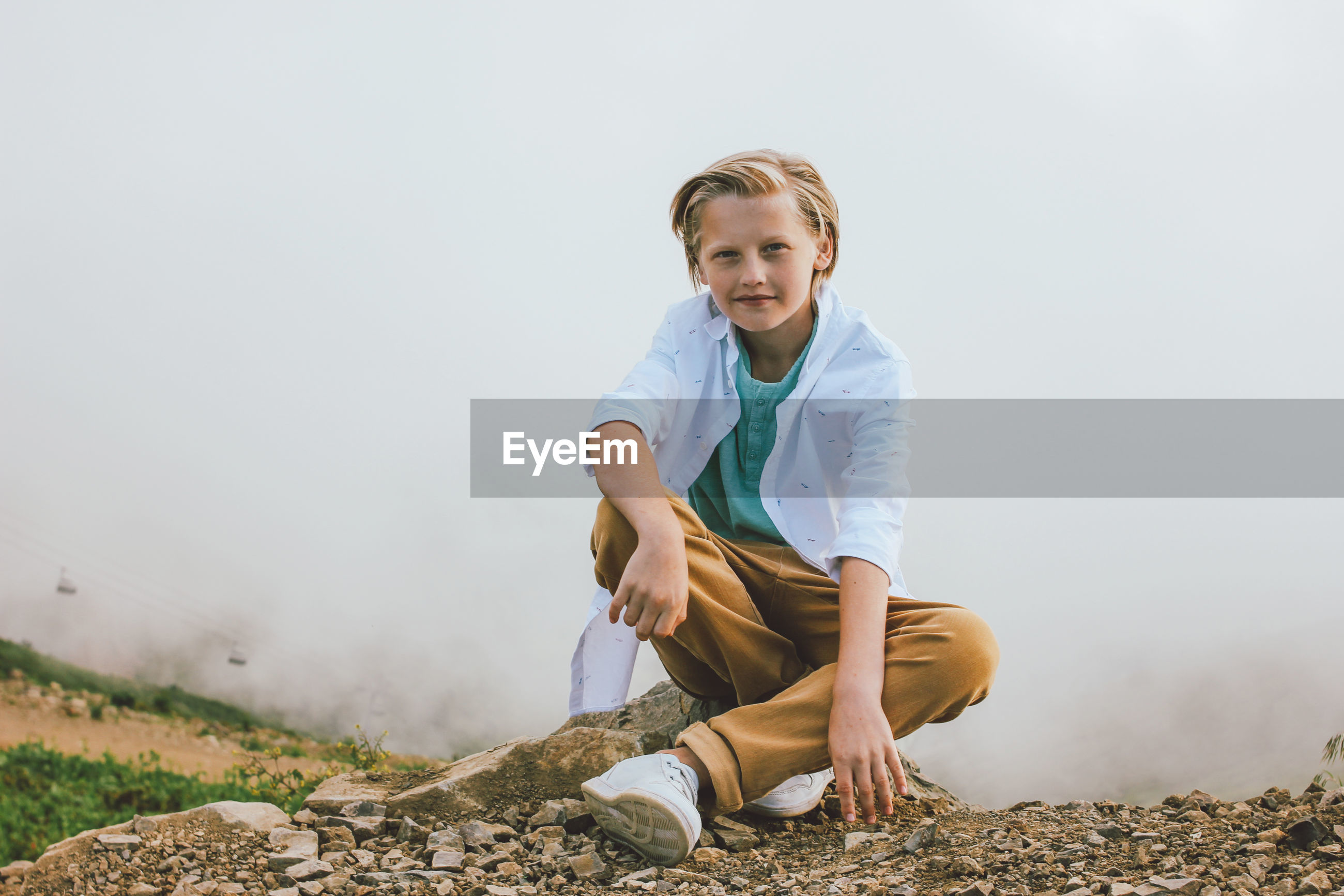 Portrait of smiling boy sitting on rock against sky