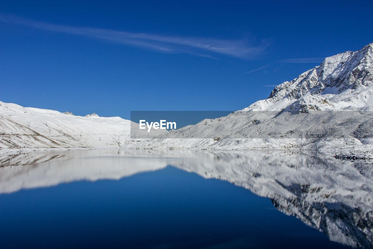 Scenic View Of Snow Covered Mountains With Reflection On Lake Against Sky