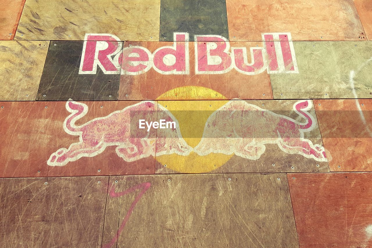 text, communication, no people, representation, western script, close-up, art and craft, creativity, animal representation, day, wood - material, sign, red, outdoors, wall - building feature, flooring, drawing - art product, pink color, multi colored, message, mural