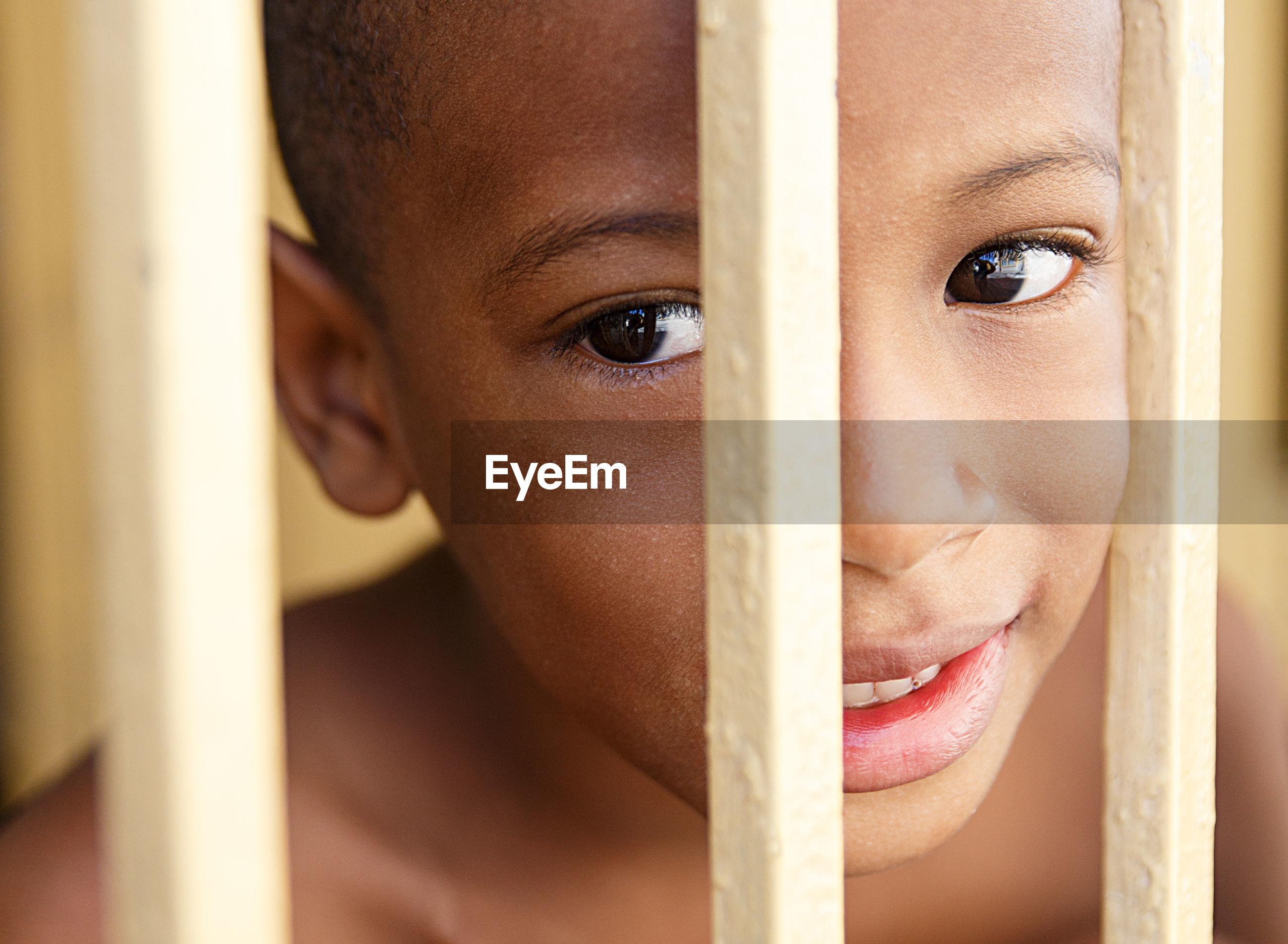 Close-up portrait of boy behind railing