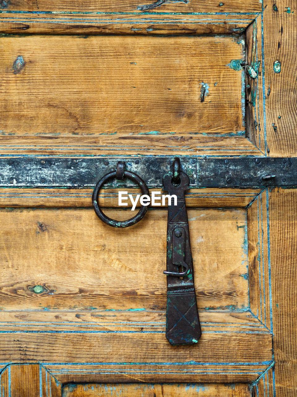 Metallic Latch And Door Knocker On Old Wooden Door